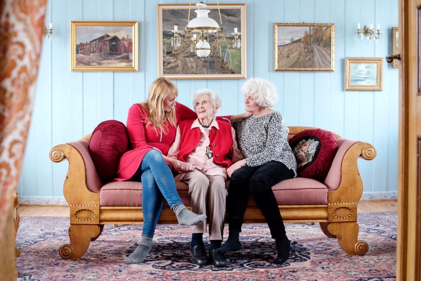 Tre generasjoner som sitter sammen i en sofa. Foto.