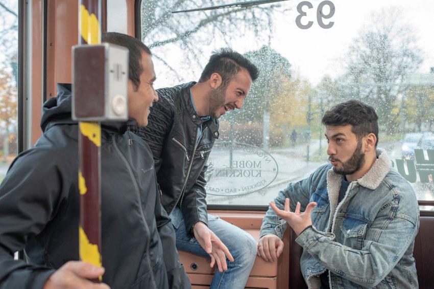 Tre menn som prater og ler inne på en trikk. Foto.