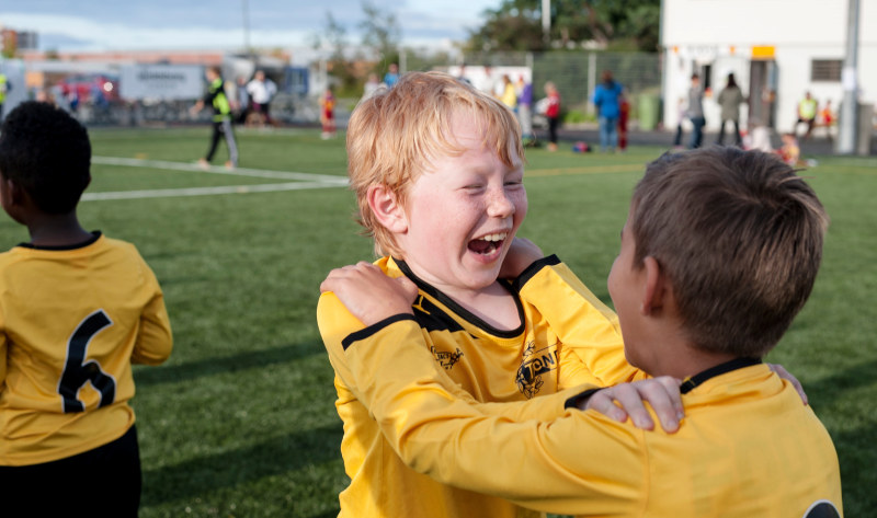 A young boy celebrating a goal on the football field. Photo.
