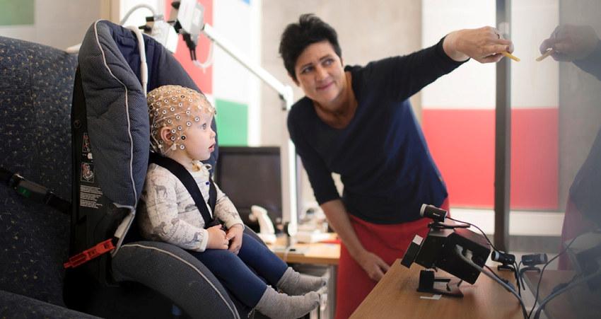 Et spedbarn med eeg-hette sammen med forsker Audrey van der Meer