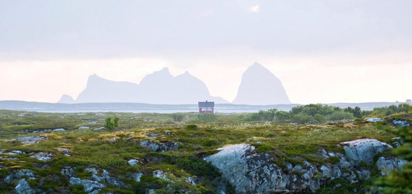 Ei lita hytte ved sjøen med Træna i bakgrunnen
