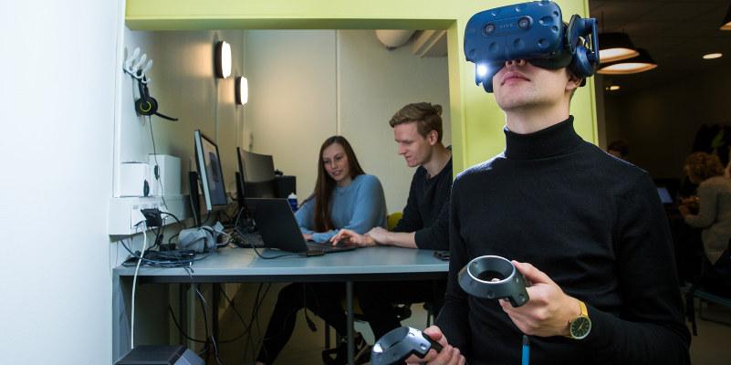 En person med VR-briller og VR-ustyr i hånda og to personer som jobber på en PC i bakgrunnen. Foto.