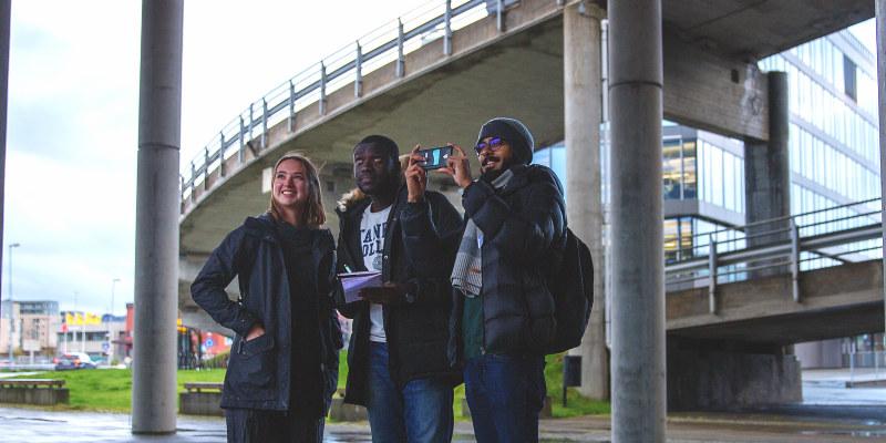Tre personer som står under et brosystem og fotograferer med en telefon. Foto.