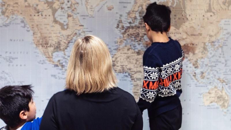 Et barn står med ryggen til og peker på et verdenskart. Det sitter en dame og et barn og ser på. Foto.