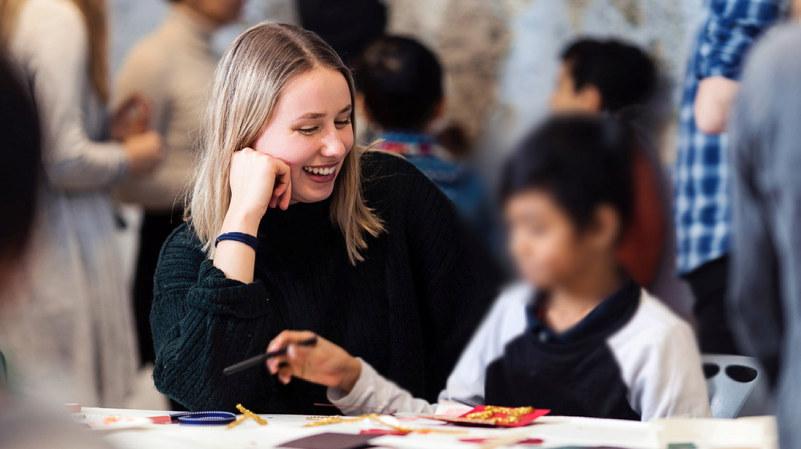 Smilende kvinnelig student som sitter sammen med et barn. Foto.