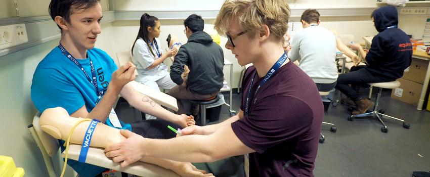 Gutter som viser hvordan en kan ta blodprøve. Foto.