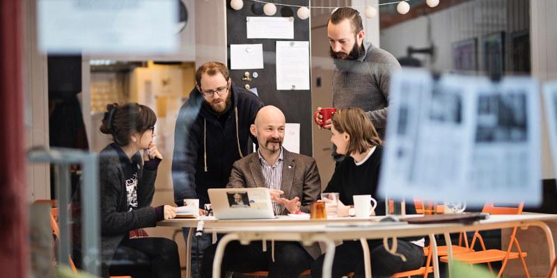 En gruppe studenter snakker med foreleseren i en gruppesituasjon. Foto.