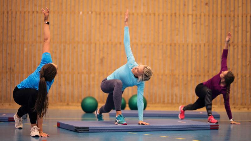 Tre kvinner som tøyer på gymmatte. Foto.
