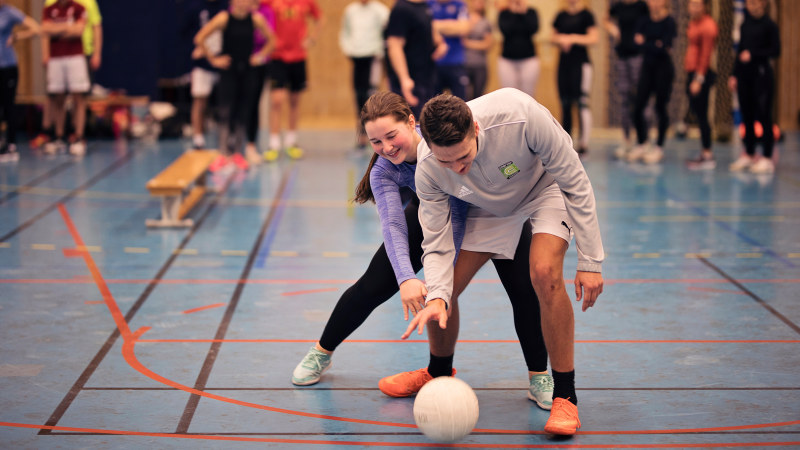 Two studentes playing handball in a sports hall. Photo.