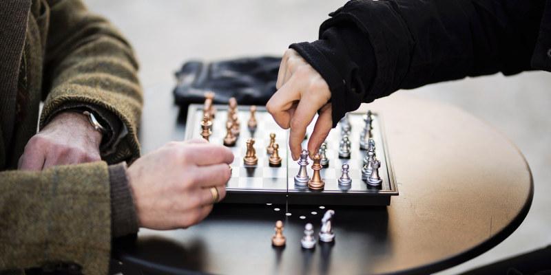 To hender som flytter sjakkbrikker. Foto.