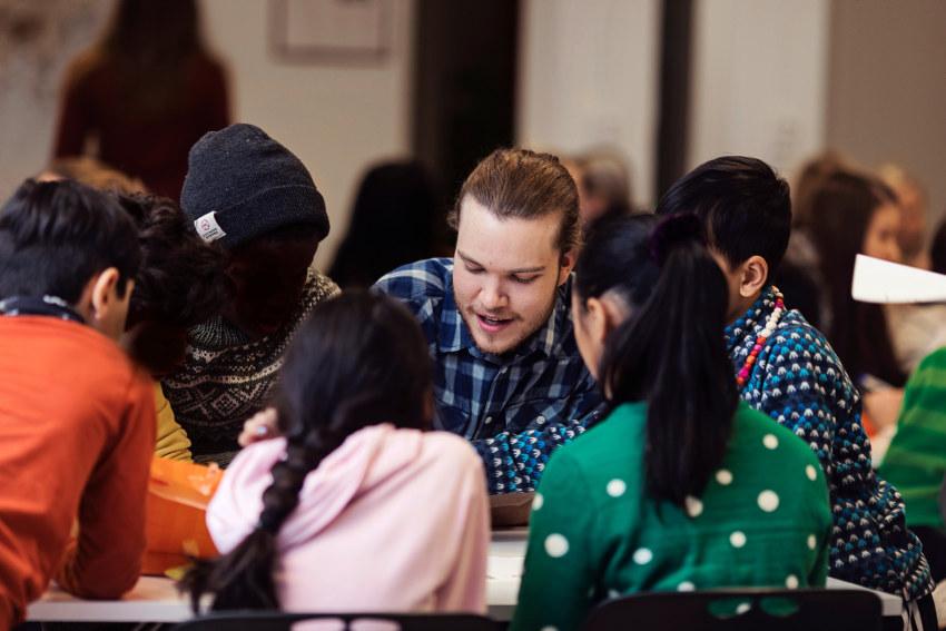 En mannlig student som sitter ved et bord sammen med barn. Foto.