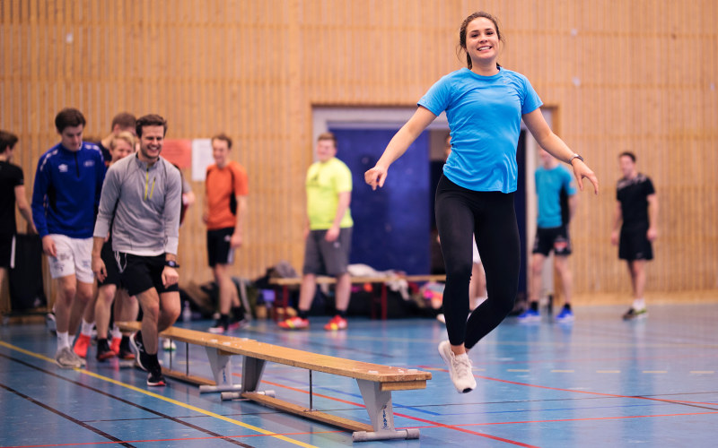 A girl jumping from a bench in a sports hall. Photo.