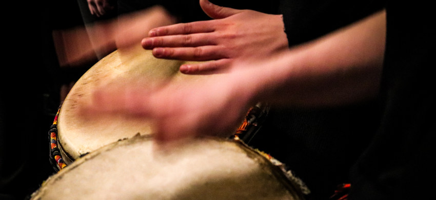 Hender som spiller på trommer. Foto.
