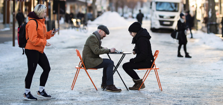 Man and woman playing chess in the street during winter. Photo.