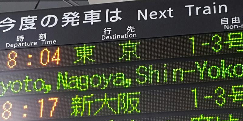 Tavle fra togstasjon med skrift på engelsk og japans. Foto.