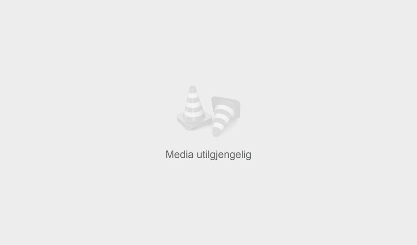 Two people sitting in the street playing chess, both are looking at the camera and smiling. Photo.