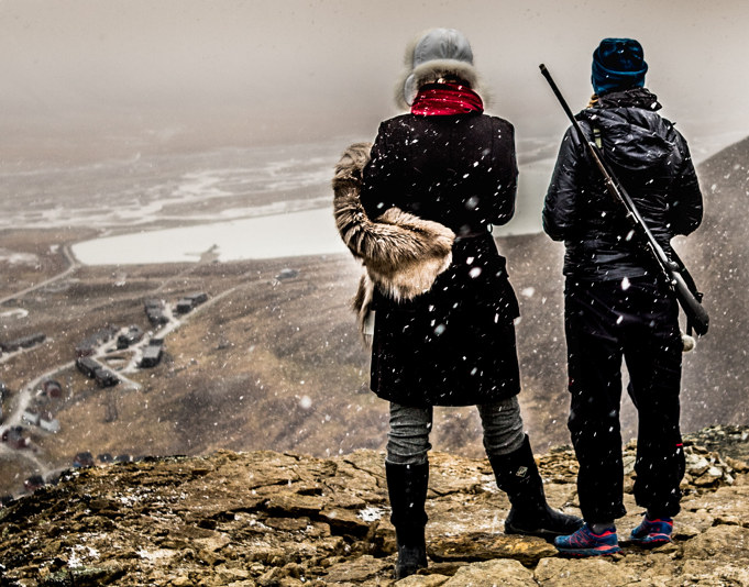 Two people standing on a mountain looking out over a field, one person is carrying a hunting rifle. Photo.