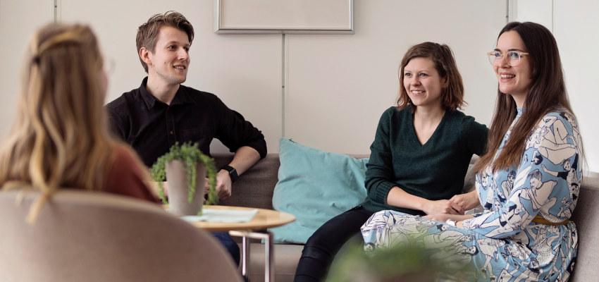 Studenter sitter sammen og smiler. Foto.