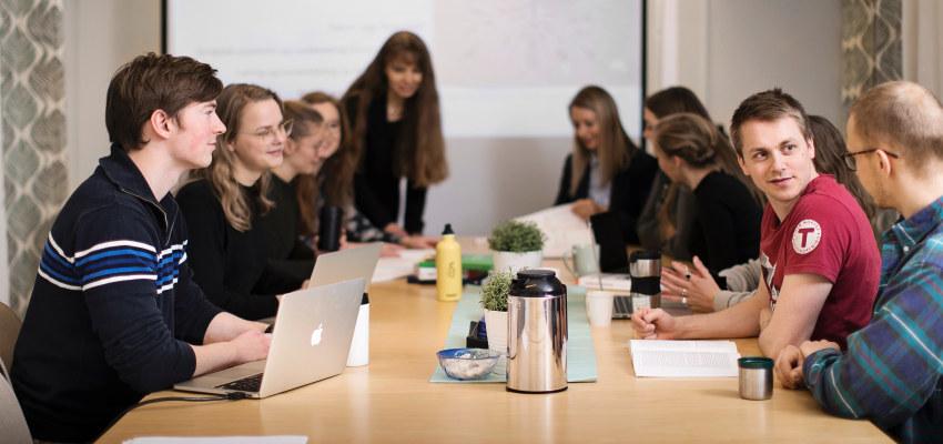 Studenter har undervisning rundt et bord. Foto.