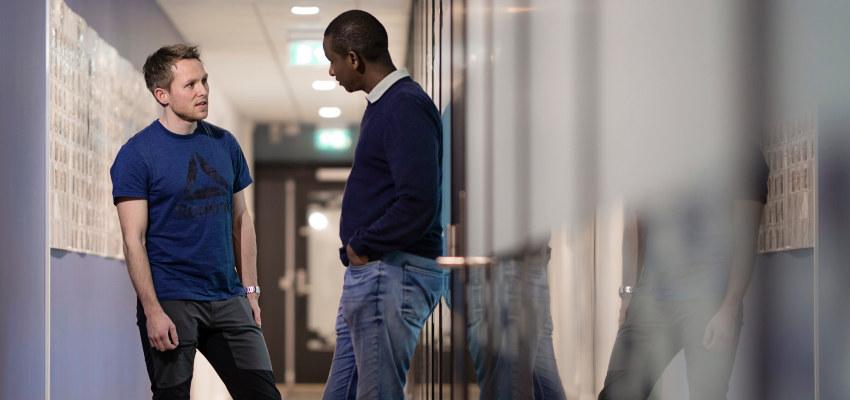 To menn som snakker sammen. Foto.