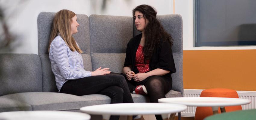 To personer sitter og prater i en sofa. Foto.