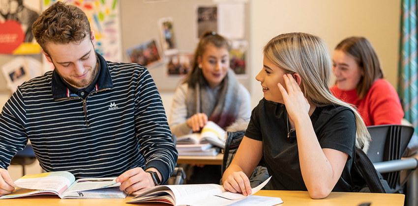 To elever sitter ved en pult og snakker sammen. Foto.