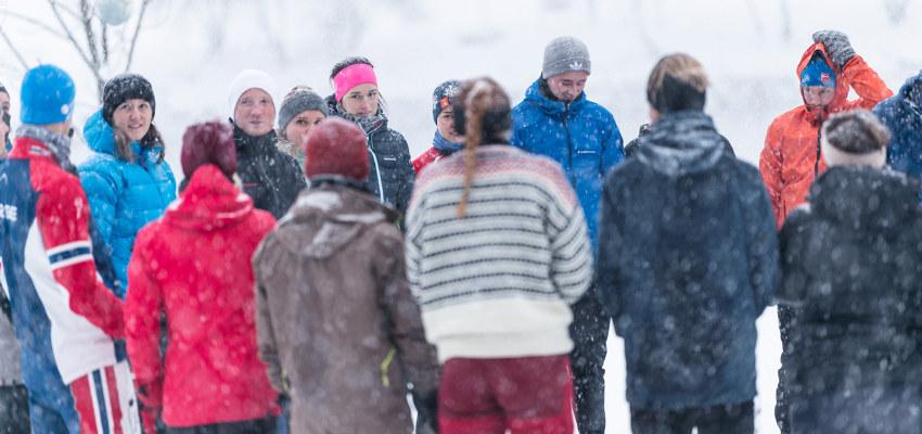 En gruppe personer står ute i snøen. Foto.