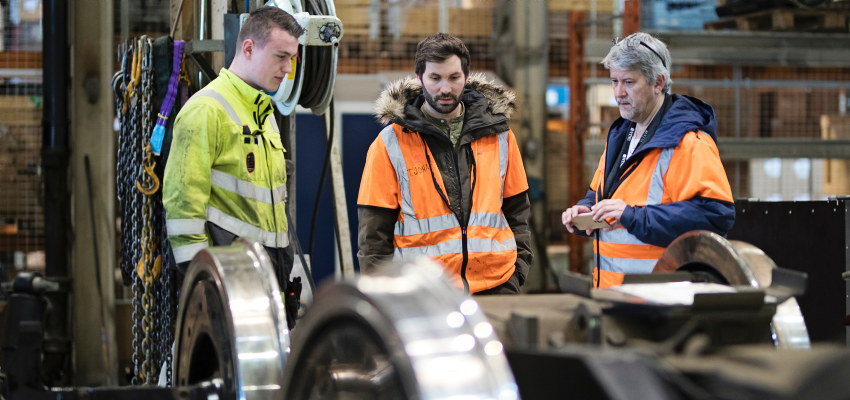 Three people looking at train wheels. Photo.
