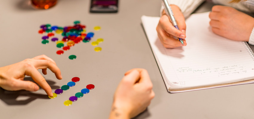 En person gjør matematiske regnestykker med knapper. Foto.