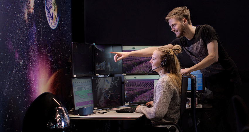 Two people looking at a screen in a space control room. Photo.
