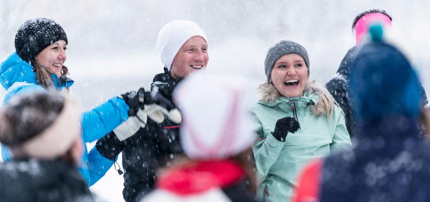Tre personer står ute i snøen. Foto.