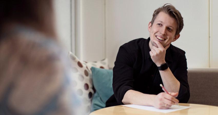 Person som sitter ved et bord og smiler. Foto.