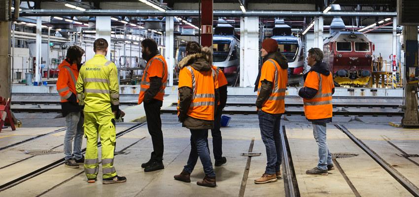 Seks personer i en togstall. Foto.