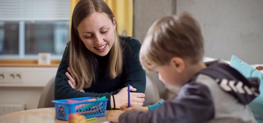 Psykolog som ser på et barn som tegner. Foto.