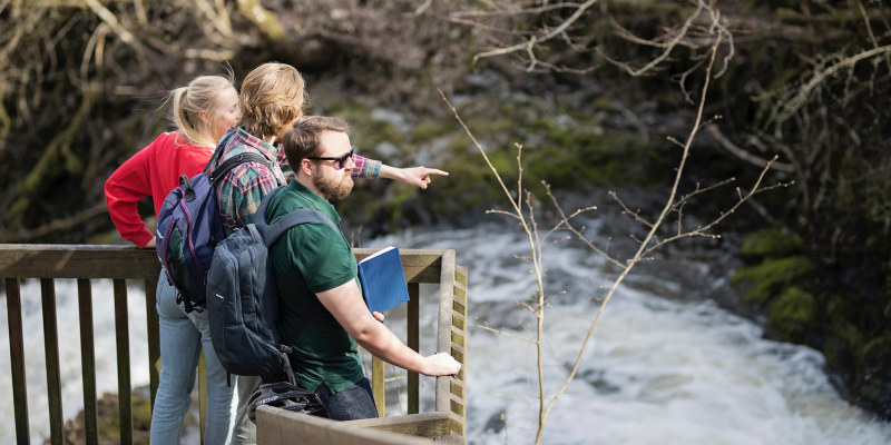 Three people looking at a waterfall. Photo.
