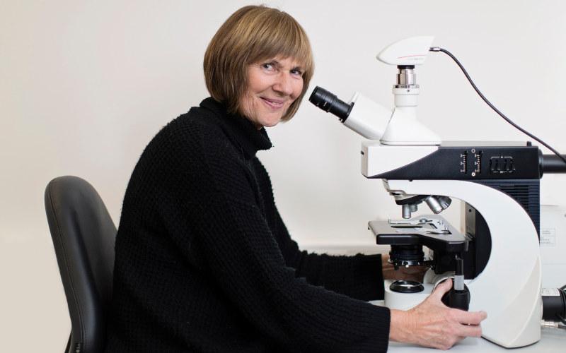Bente Berg sitting next to a microscope. Photo.