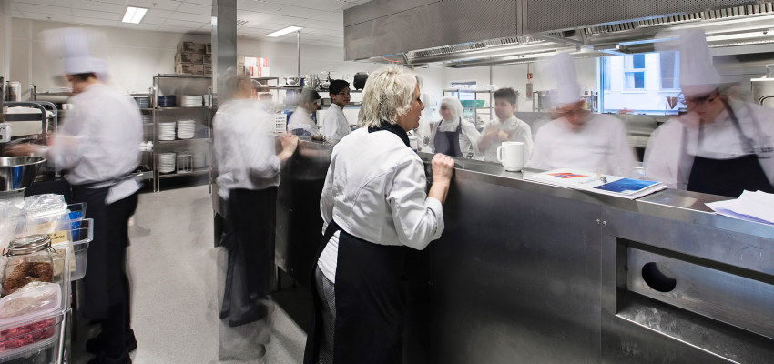 Lærer og elever i et skolekjøkken. Foto.