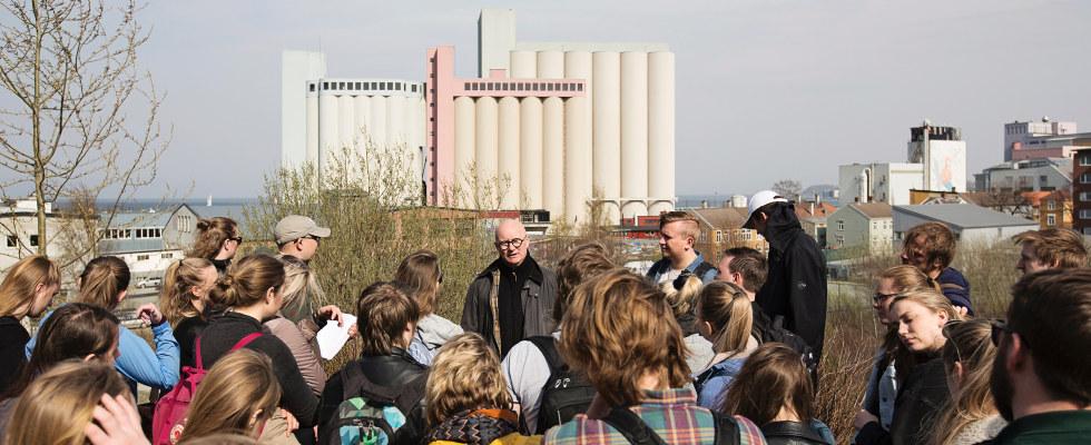 En gruppe folk foran en fabrikk. Foto.