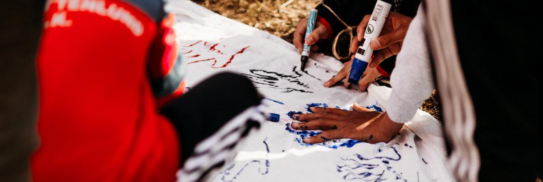 Elever som tar avtrykk av hendene sine. Foto