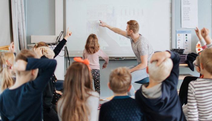 Skoleklasse og lærer i tavleaktivitet. Hender i været. Foto