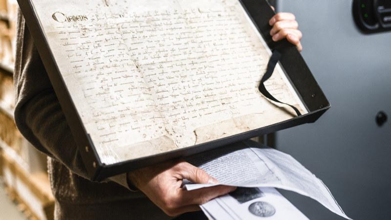 Person som viser frem arkivert dokument. Foto