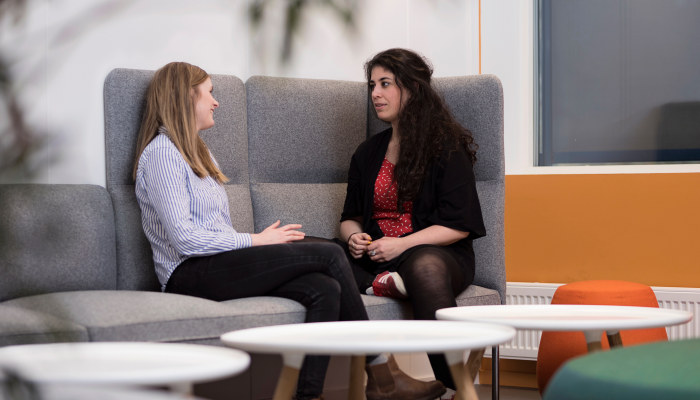To personer sitter og snakker sammen i en sofa. Foto.