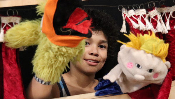 A child holding two hand puppets. Photo
