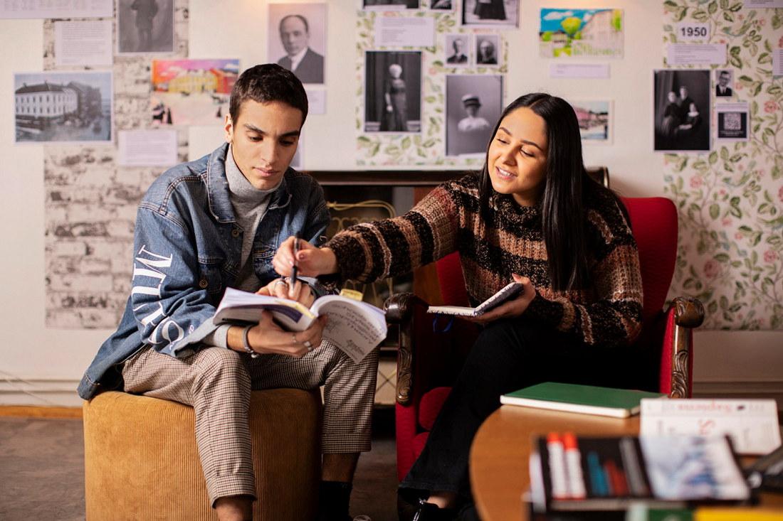 To studenter sitter i en sofa og ser i en bok sammen. Foto.