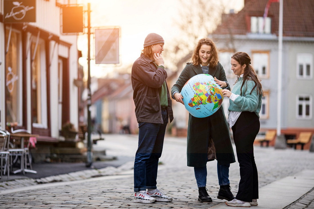 Tre studenter står i en gate og hodler en stor globus mellom seg. Foto.
