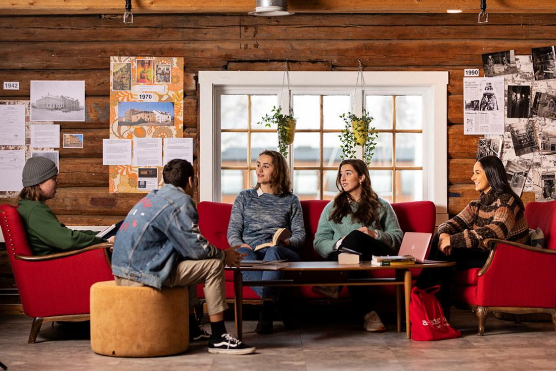 Fem studenter sitter i en sofagruppe rundt et bord med bøker og data. Foto.