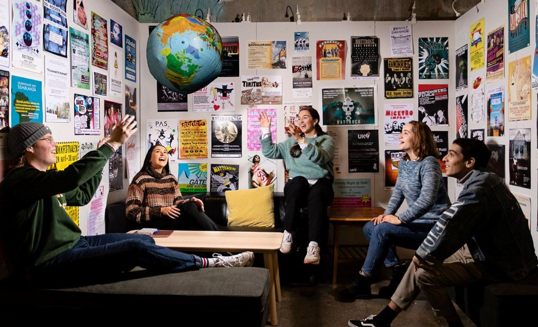 Fem studenter sitter i et rom med plakater på veggene, kaster en globus-ball opp i lufta og ler. Foto