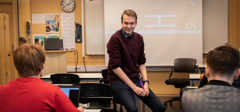 Lærerstudent i klasserom. Smiler til elever. Foto.