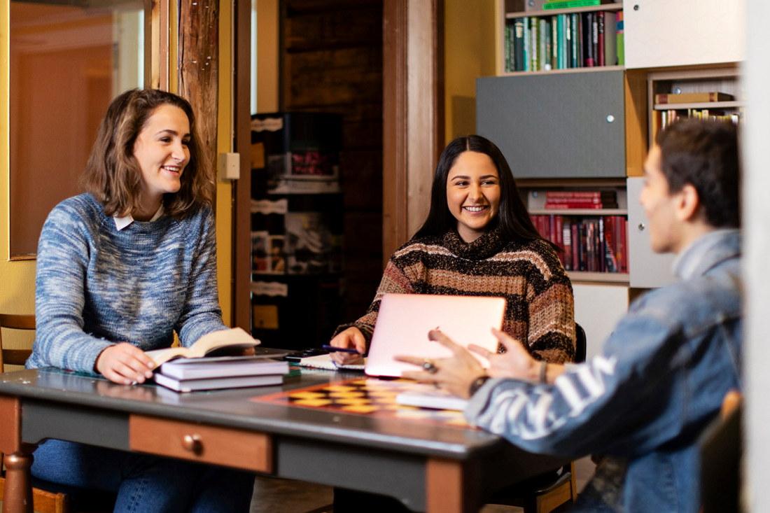 Tre studenter sitter rundt et bord med bøker og en data foran seg. Foto.