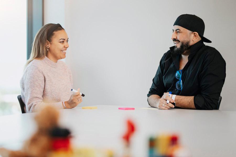 To studenter sitter ved bordet og smiler til hverandre. foto.